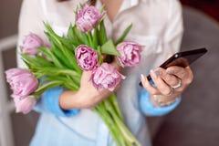 Młoda kobieta texting na jej smartphone z spojrzeniem koncentracja gdy stoi przeciw błękitnej ścianie zdjęcia royalty free