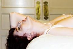 Młoda Kobieta toples Z głową Nad krawędzią łóżko zdjęcie stock