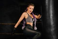 Młoda kobieta trenuje w bokserskim pierścionku z ciężką uderza pięścią torbą Fotografia Stock