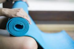 Młoda kobieta trzyma błękitną joga matę obrazy royalty free