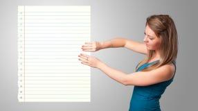 Młoda kobieta trzyma białą papierowej kopii przestrzeń z diagonalnymi liniami Zdjęcie Royalty Free