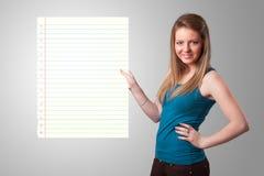 Młoda kobieta trzyma białą papierowej kopii przestrzeń z diagonalnymi liniami Zdjęcie Stock