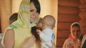 Młoda kobieta trzyma dziecka w rękach i robi znakowi krzyż w kościół zbiory