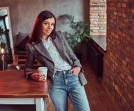 Młoda kobieta trzyma filiżankę takeaway kawa ubierał w szarej eleganckiej kurtce podczas gdy opierający na stole w pokoju z loft zdjęcie stock