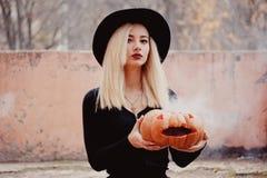 Młoda kobieta trzyma Halloween dyniowy z wewnątrz go w jesieni w czarnym żakiecie z białym dymnym przybyciem obrazy royalty free