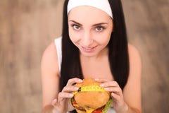 Młoda kobieta trzyma hamburger w pomiarowej taśmie Dziewczyny stojaki na drewnianym tle najlepszy widok Pojęcie on Obraz Stock