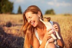 Młoda kobieta trzyma Jack Russell teriera szczeniaka na jej ręce, tryi zdjęcia royalty free