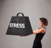 Młoda kobieta trzyma jeden tonę stresu ciężar Fotografia Stock