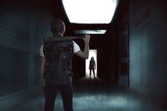 Młoda kobieta trzyma kij bejsbolowy pozycję w zmroku korytarza wi Zdjęcie Stock