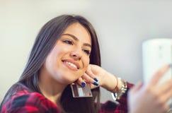 Młoda kobieta trzyma kredytową kartę i patrzeje telefon Obrazy Royalty Free