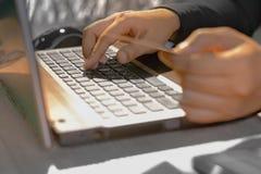 Młoda kobieta trzyma kredytową kartę na laptopie dla onlinego zakupy pojęcia Obrazy Royalty Free