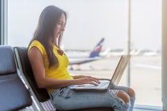 Młoda kobieta trzyma laptop na podołek pisać na maszynie klawiaturze indoors w lotnisku obrazy stock