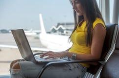 Młoda kobieta trzyma laptop na podołek pisać na maszynie klawiaturze indoors w lotnisku obrazy royalty free