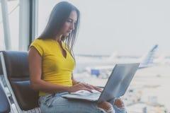 Młoda kobieta trzyma laptop na podołek pisać na maszynie klawiaturze indoors w lotnisku zdjęcia royalty free