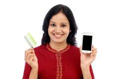 Młoda kobieta trzyma mądrze telefon i kredytową kartę Obraz Royalty Free