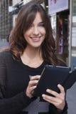 Młoda kobieta trzyma pastylkę na ulicie obrazy stock