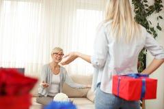 Młoda kobieta trzyma prezenta pudełko za plecy dla jej matki salon wygodnie zdjęcie royalty free