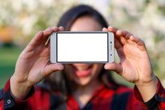 Młoda kobieta trzyma smartphone z pustym bielu ekranem przed ona z dwa rękami Z miejscem minować przestrzeń Outdoors, fotografia royalty free