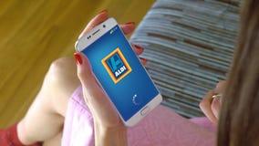 Młoda kobieta trzyma telefon komórkowego z ładować ALDI wiszącą ozdobę app Konceptualny artykułu wstępnego CGI Zdjęcia Stock