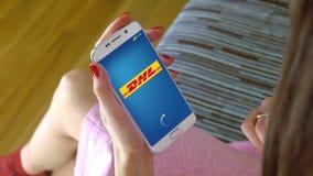 Młoda kobieta trzyma telefon komórkowego z ładować DHL wiszącą ozdobę app Konceptualny artykułu wstępnego CGI Obrazy Stock