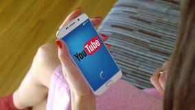 Młoda kobieta trzyma telefon komórkowego z ładować YouTube wiszącą ozdobę app Konceptualny artykułu wstępnego CGI Zdjęcia Royalty Free