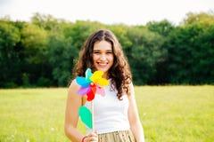 Młoda kobieta trzyma wiatraczek zabawkę Obrazy Royalty Free