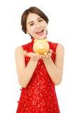 Młoda kobieta trzyma złotego prosiątko banka szczęśliwego nowego roku chiński Fotografia Royalty Free