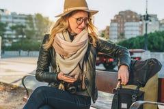Młoda kobieta turysta, modniś dziewczyna siedzi na ławce w miasto ulicie, jest przyglądający dla coś w jej plecaku Wakacje, podró Zdjęcia Stock