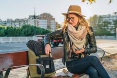 Młoda kobieta turysta, modniś dziewczyna siedzi na ławce w miasto ulicie, jest przyglądający dla coś w jej plecaku Wakacje, podró Fotografia Royalty Free