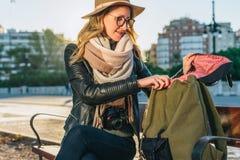 Młoda kobieta turysta, modniś dziewczyna siedzi na ławce w miasto ulicie, jest przyglądający dla coś w jej plecaku Wakacje, podró Obrazy Royalty Free