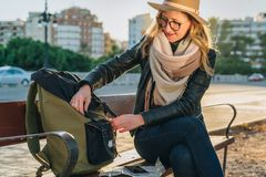 Młoda kobieta turysta, modniś dziewczyna siedzi na ławce w miasto ulicie, jest przyglądający dla coś w jej plecaku Wakacje, podró Obrazy Stock