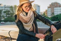 Młoda kobieta turysta, modniś dziewczyna siedzi na ławce w miasto ulicie, jest przyglądający dla coś w jej plecaku Wakacje, podró Obraz Royalty Free