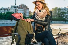 Młoda kobieta turysta, modniś dziewczyna siedzi na ławce w miasto ulicie, jest przyglądający dla coś w jej plecaku Wakacje, podró Zdjęcia Royalty Free