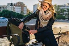 Młoda kobieta turysta, modniś dziewczyna siedzi na ławce w miasto ulicie, jest przyglądający dla coś w jej plecaku Wakacje, podró Zdjęcie Royalty Free