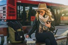 Młoda kobieta turysta, modniś dziewczyna siedzi na ławce w miasto ulicie, jest przyglądający dla coś w jej plecaku Wakacje, podró Obraz Stock