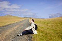 Młoda kobieta turysta siedzi na drodze zdjęcie stock