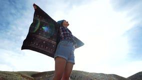 Młoda kobieta turysta w deseniowym żakiecie stoi przy krawędzią czerwona góra i rozprzestrzenia ona jak skrzydłami ręki Chce zbiory