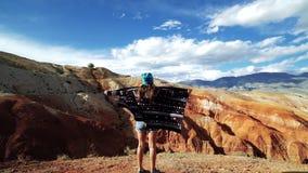 Młoda kobieta turysta w deseniowym żakiecie stoi przy krawędzią czerwona góra i rozprzestrzenia ona jak skrzydłami ręki Chce zdjęcie wideo