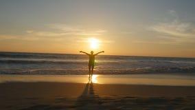 Młoda kobieta turysta z plecaka odprowadzeniem na plaży ocean przy zmierzchem i podnosić rękami Dziewczyna wycieczkowicz iść na p Zdjęcia Royalty Free