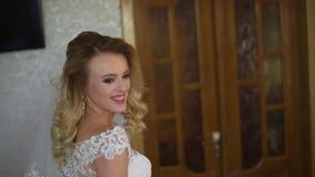 Młoda kobieta uśmiechy, pozować przy kamerą i pokazywać suknię, swobodny ruch zbiory