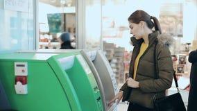 Młoda kobieta używa ATM maszynę Dziewczyna prowadzi gotówkową maszynę mieć niektóre pieniądze w centrum handlowym pojęcia tła die zbiory
