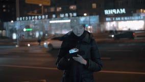 Młoda kobieta używa cyfrową pastylkę w ruchliwie nocy mieście zbiory