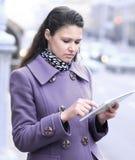 Młoda kobieta używa cyfrową pastylki pozycję na miasto ulicie Obraz Stock