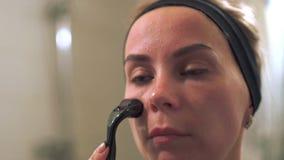 Młoda kobieta używa derma rolownika dla twarzy Rolownik, microneedle, mesotherapy zdjęcie wideo
