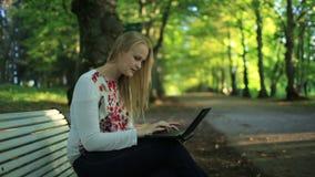 Młoda kobieta używa jej laptop w parku zdjęcie wideo