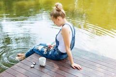 Młoda kobieta używa jej smartphone obsiadanie na molu i pijący gorącą kawę zdjęcia stock