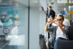Młoda kobieta używa jej telefon komórkowego podczas gdy czekający wsiadać samolot zdjęcia stock
