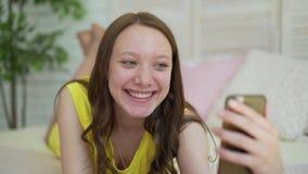 Młoda Kobieta Używa komórka Mądrze telefonu dziewczyny Szczęśliwego Uśmiechniętego Pięknego lying on the beach Na łóżku W sypialn zbiory