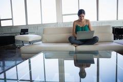 Młoda kobieta używa laptop przy biurem podczas gdy siedzący na kanapie zdjęcia royalty free