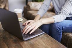 Młoda kobieta używa laptop w sklep z kawą, w połowie sekcja fotografia stock
